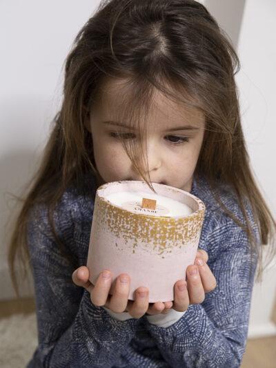 enfant qui tient une bougie dans un pot rose